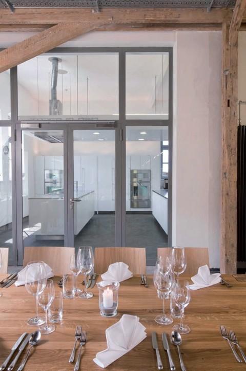Schlicht klassisch dekorierter Esstisch und blick auf den Gruppen-Kochbereich
