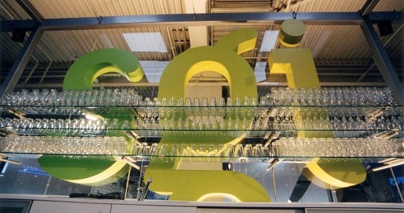 Weit überspannendes Gläserregal mit Glasfachböden vor 3 Meter hohen 3-D Buchstaben
