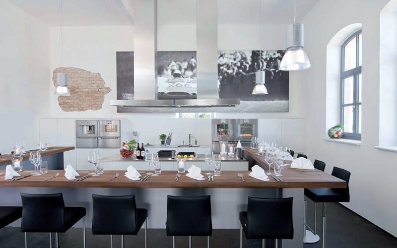 Showküche in weiß und Edelstahl mit Zuschauer- und Gästebar in Nussbaum Holz